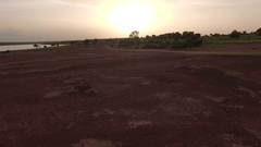 An arid African plain of red earth near a lake. Aerial video Stock Footage