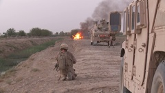 Marine crouches down near his Humvee while vehicle in road is in flames Stock Footage