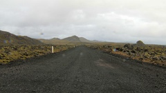 Ground road through lava field, mountains on sides, icelandic landscape in rainy Stock Footage