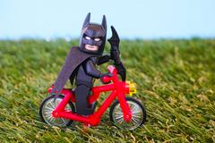 Lego Batman riding bike on grass background Kuvituskuvat