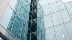 Close-up low angle steadicam shot of modern glass facade office building in Stock Footage