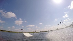 A man jumping his wakeboard off a ramp at a cable park, slow motion. Stock Footage