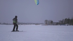 A young man caught wind of the kite and he was drawn on the snow, 4k Stock Footage