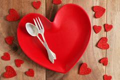 Heart Shaped Dinner Plate with Fine Silverware on Wood Plank Table Stock Photos