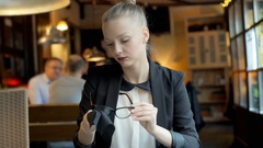 Businesswoman sitting in the cafe and cleaning her glasses with a cloth, steady Stock Footage