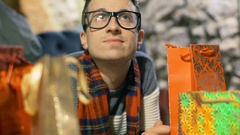 Man looking on the presents and wearing tartan scarf, steadycam shot Stock Footage