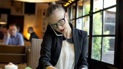 Businesswoman checking papers and speaking on cellphone in the cafe, steadycam  Stock Footage