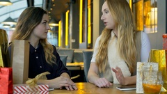 Girls having an argument in the cafe and look offended, steadycam shot Stock Footage