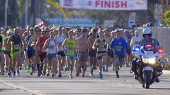 A crowd of people running at the start of a 10K race. Stock Footage