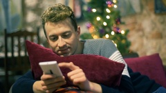 Man using smartphone and smiling to the camera while sitting on comfy couch, ste Stock Footage