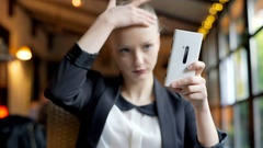 Beautiful businesswoman checking her appearance in smartphone, steadycam shot Stock Footage
