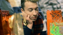 Man looking on presents and having a dilemma, steadycam shot Stock Footage