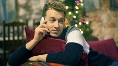 Man chatting on cellphone and smiling to the camera while sitting on comfy couch Stock Footage