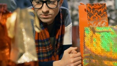 Thoughtful man wearing tartan scarf and looking on presents, steadycam shot Stock Footage