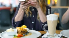 Girls having lunch in the cafe and doing photos of the desserts, steadycam shot Stock Footage