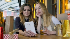 Girls sitting in the cafe and having a videchat on tablet, steadycam shot Stock Footage