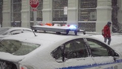 Police car turret lights flashing and man crossing street in snow storm NYC Stock Footage