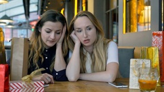 Two, sad girls sitting in the cafe and talking with each other, steadycam shot Stock Footage