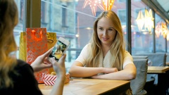 Girl doing photo of her best friend on smartphone in the festive cafe, steadycam Stock Footage