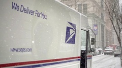 Snowing on USPS we deliver for you slogan on mail delivery truck parked NYC Stock Footage