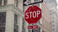 Snowing with all way stop sign and one way arrow in snow storm blizzard NYC Stock Footage