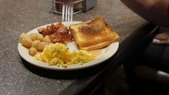 A dolly shot of a man eating bacon eggs and french toast Stock Footage