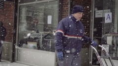 USPS postal delivery worker mailman pushing dolly in snow storm snowing NYC Stock Footage