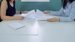 Office workers sitting opposite each other working with documents Stock Footage