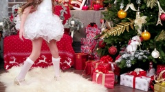 Little girl looking gifts, child carnival costume near the Christmas tree Stock Footage