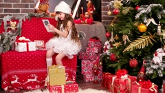 Little girl lays out the name cards on Christmas gifts Stock Footage