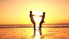 Happy couple turning round on beach during sunset, super slow motion 240fps Stock Footage