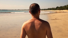 Young man walking on beach during sunny day, super slow motion 240fps Stock Footage