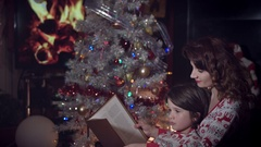 4k Christmas and New Year Holiday Mom and Son Reading Book Stock Footage