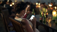 Young woman texting on smartphone in beach bar at night  Stock Footage