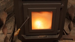Dolly shot of a pellet stove heating a room Stock Footage