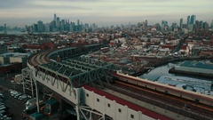 Camera flies high over an elevated track as subway heads off toward Manhattan Stock Footage