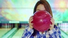 Girl looks out from behind the bowling ball Stock Footage