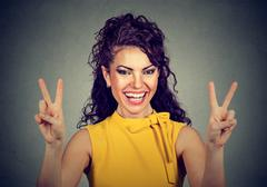 Smiling woman in yellow dress showing victory or peace sign Stock Photos