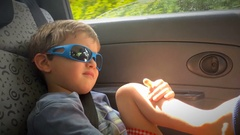 Child sitting in passenger seat and wearing sunglasses. Kid going to the beach d Stock Footage