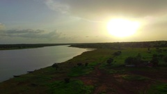 A green African plain of red earth near a river. Aerial video Stock Footage