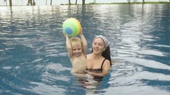 Woman and little cute girl playing in pool Stock Footage