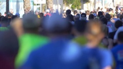 The back of a crowd of people running in a 10K race, slow motion. Stock Footage