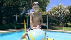 Child riding inflatable toy inside swimming pool Stock Footage