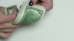 Placing a stack of two dollars bills on a desk Stock Footage
