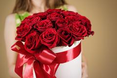 Girl holding in hand rich gift bouquet of 21 red roses. Composition of flow.. Kuvituskuvat