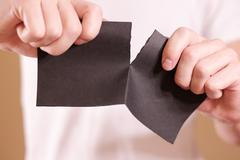 Man tearing a piece of paper in half blank black flyer brochure booklet. Le.. Stock Photos