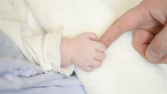 A new father holds his newborn infant baby's hand Stock Footage