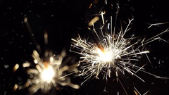 Firework sparkler burning with dancing snowflakes against night sky. Stock Footage