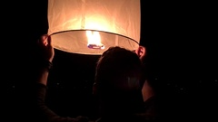 Young couple launching a red Chinese sky fly fire lantern to make a wiss on the Stock Footage