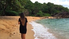 Young woman in black dress walking along the seaside at secret beach and Stock Footage